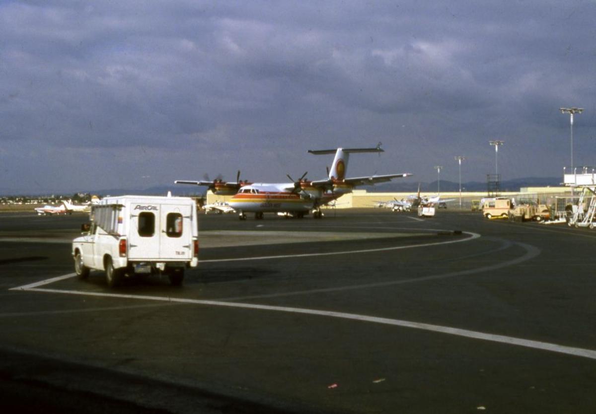 Lufthavn/Flyplass. Et fly, DHC-7 ( Dash7) fra flyselskapet Golden West, klar til å parkere.