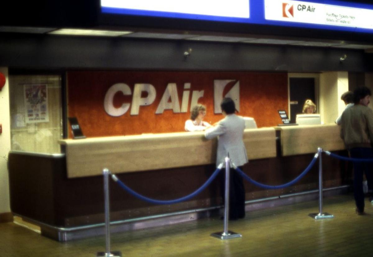 Lufthavn/Flyplass. CP  Air med egen ekspedisjons skranke. To personer (funksjonærer) ekspederer kunder.