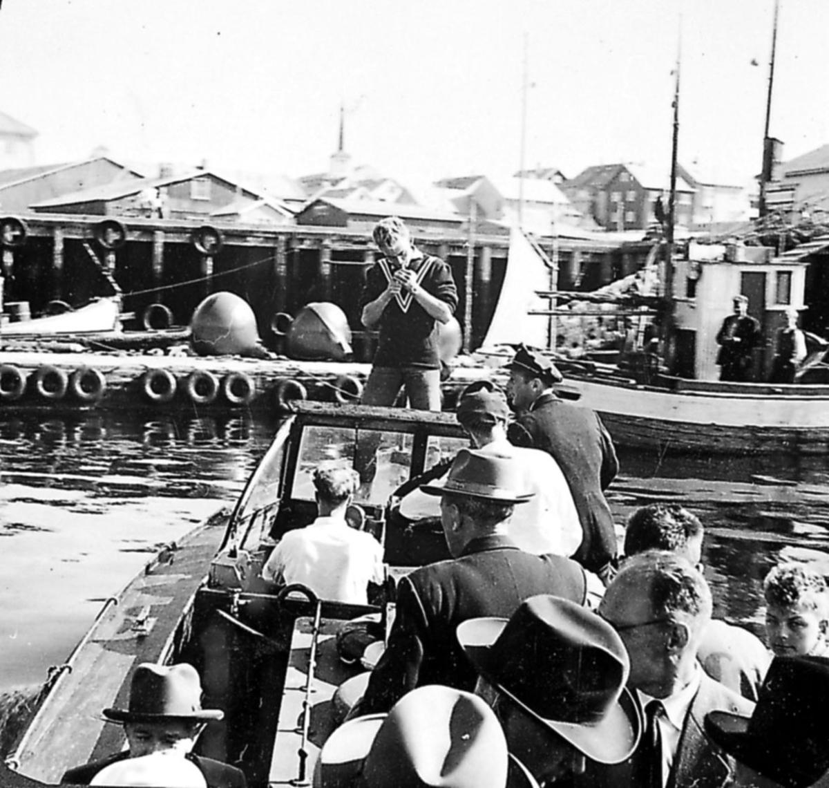 Portrett, flere personer ombord i fly-passasjerbåt, tilbringerbåt.  Kaianlegg og flere båter i bakgrunnen.