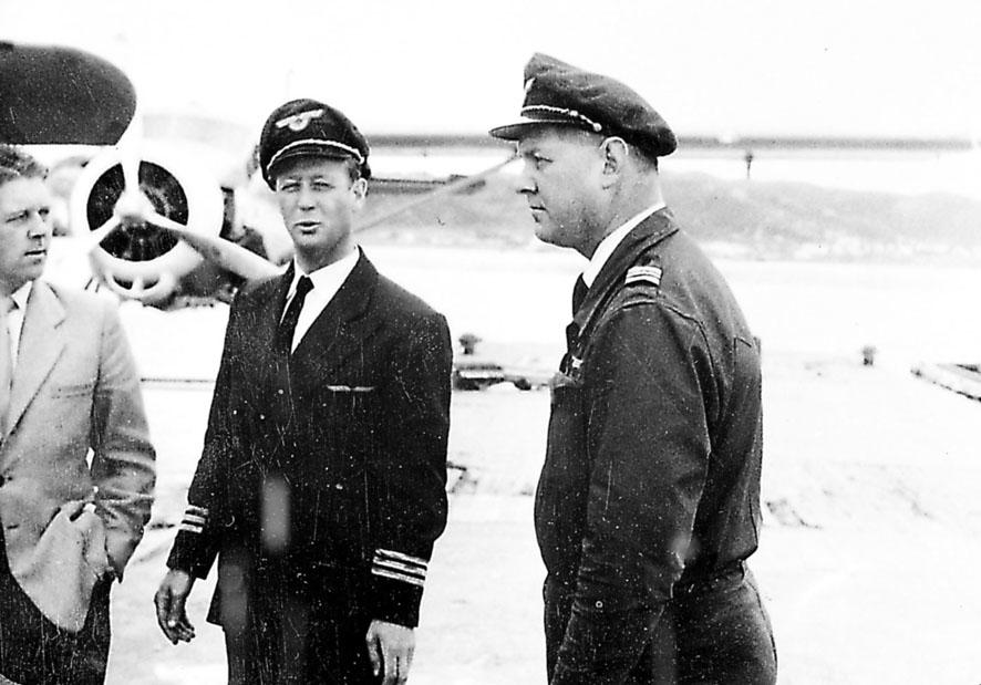 Lufthavn. Portrett, 3 personer står foran et fly, 2 i flyuniform, flypersonell.