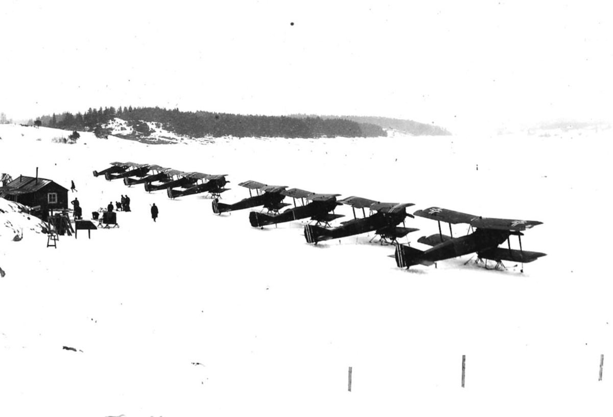Flere fly oppstilt på bakken, Kaje og en FF.7 Hauk.  Flere personer og en bygning til venstre. Snø.
