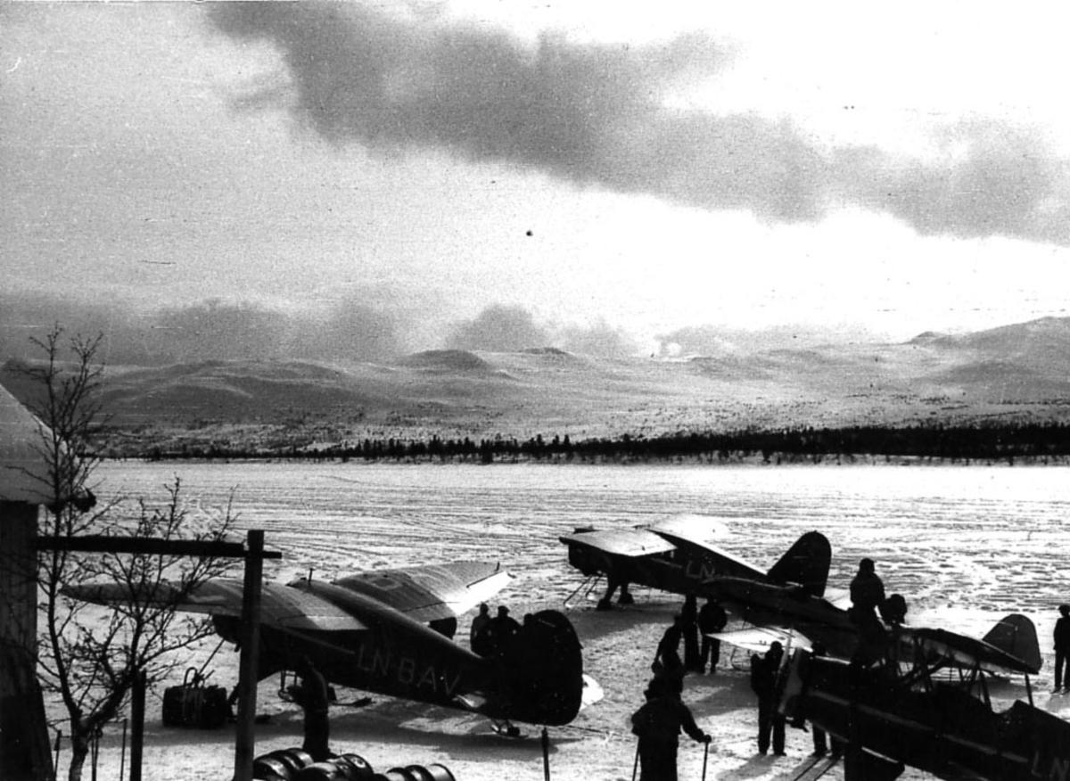Åpen plass, tre fly på bakken med skiunderstell fra Widerøe. Flere personer ved flyene.