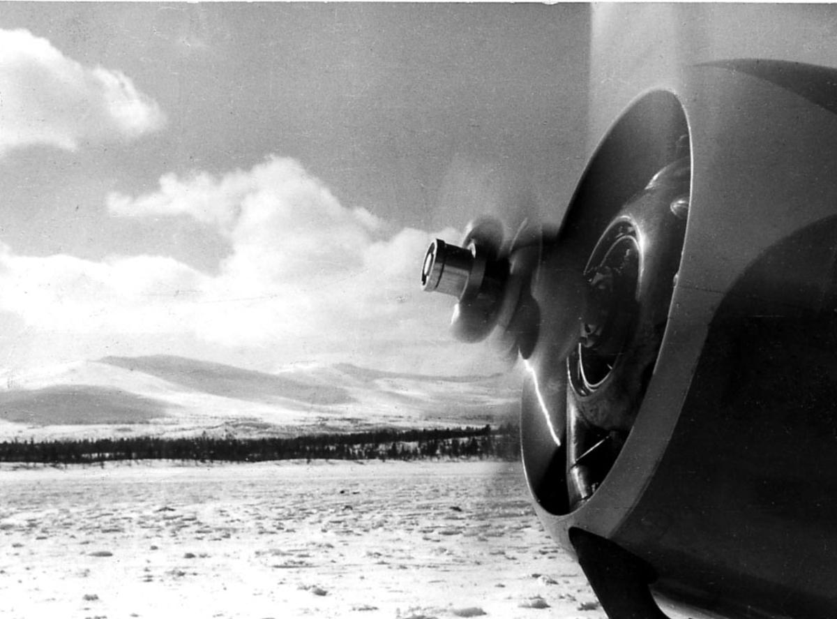 Detalj av flymotor på en propellfly fra Widerøe. Åpen plass med snø på bakken.