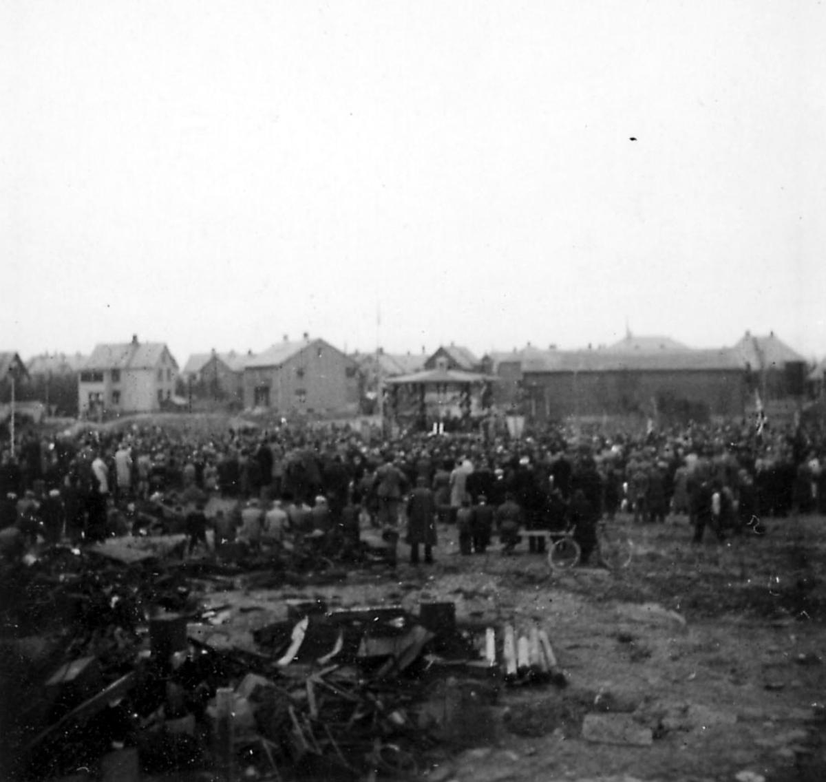 Frigjøringsdagene i Bodø etter krigen 1940 - 1945. Åpen plass med paviljong. Mange personer samlet. Rester etter ødeleggelser i forgrunnen.