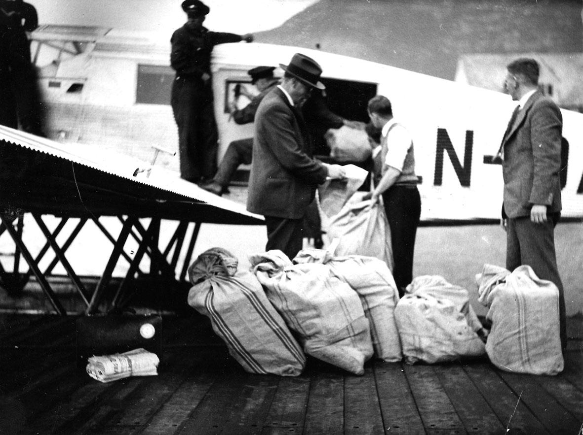 """Sjøflyhavn, flere personer, postsekker på kaia, bak ligger Ett fly ved kaia. Junkers W34, LN-DAB """"Ternen""""."""