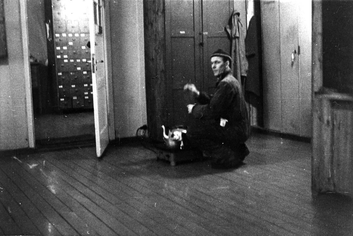 Portrett, 1 person sitter bøyd foran kokeplate på gulvet med en kjele på. Bak sees noen arkivskap el. gjennom ei døråpning.