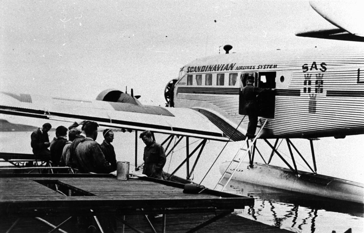 Sjøflyhavn, Ett fly i vannkanten, Junkers JU 52/3mge, fra SAS. Ligger ved en brygge. Flere personer på brygga.