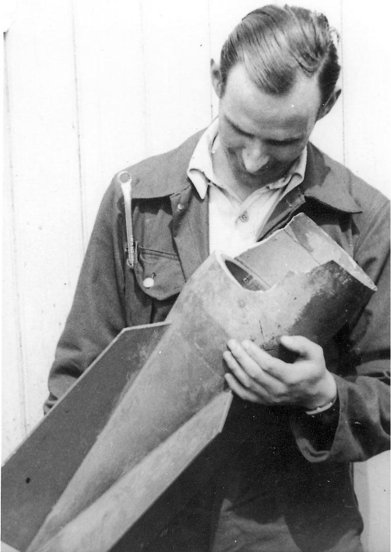 Portrett, en person, mekaniker, med noe i hendene (del til våpen/rakett for fly?)