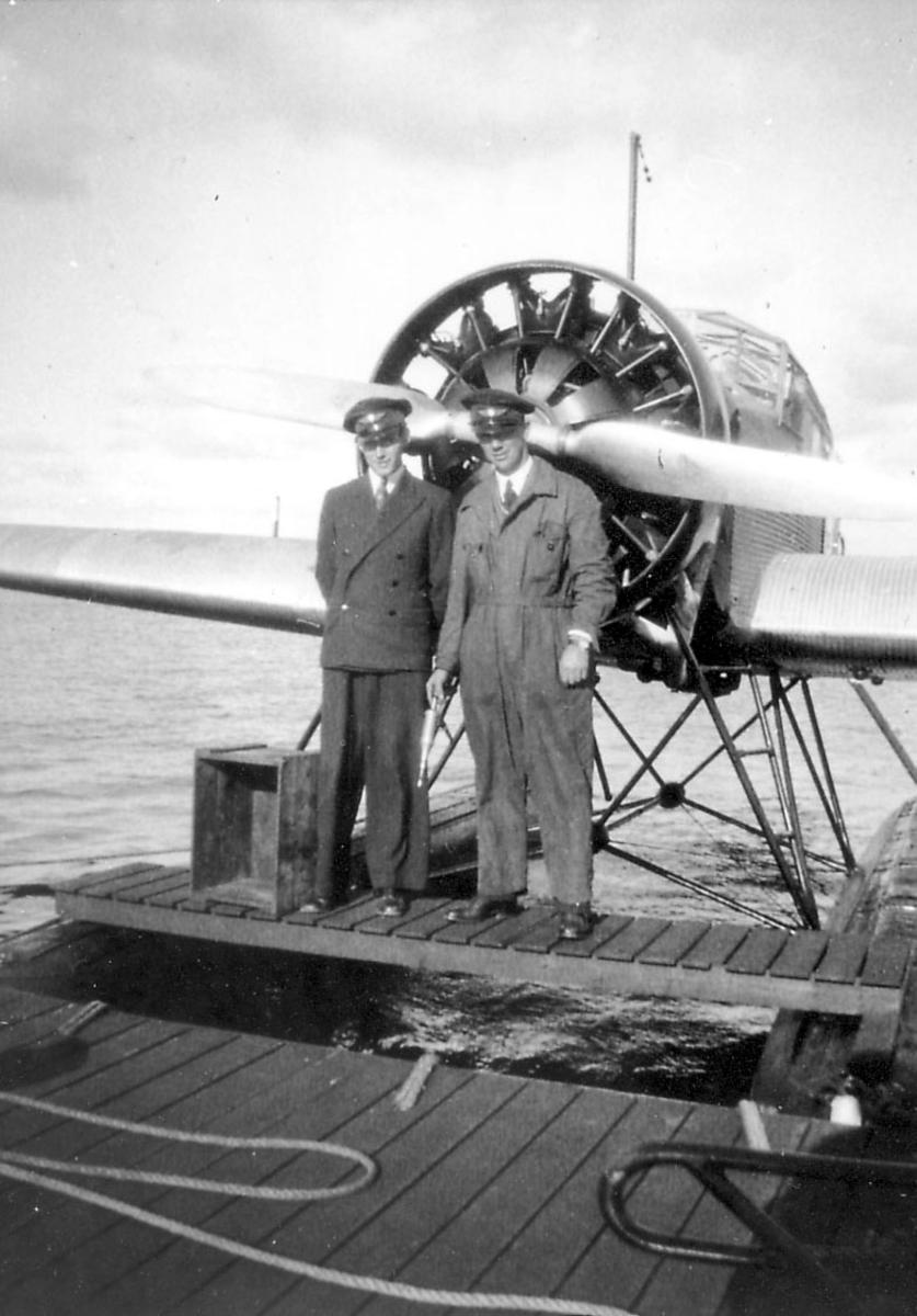 """Sjøflyhavn - brygge, to personer står foran motoren til ett fly, Junkers Ju W 34 """"Ternen"""", LN-DAB."""