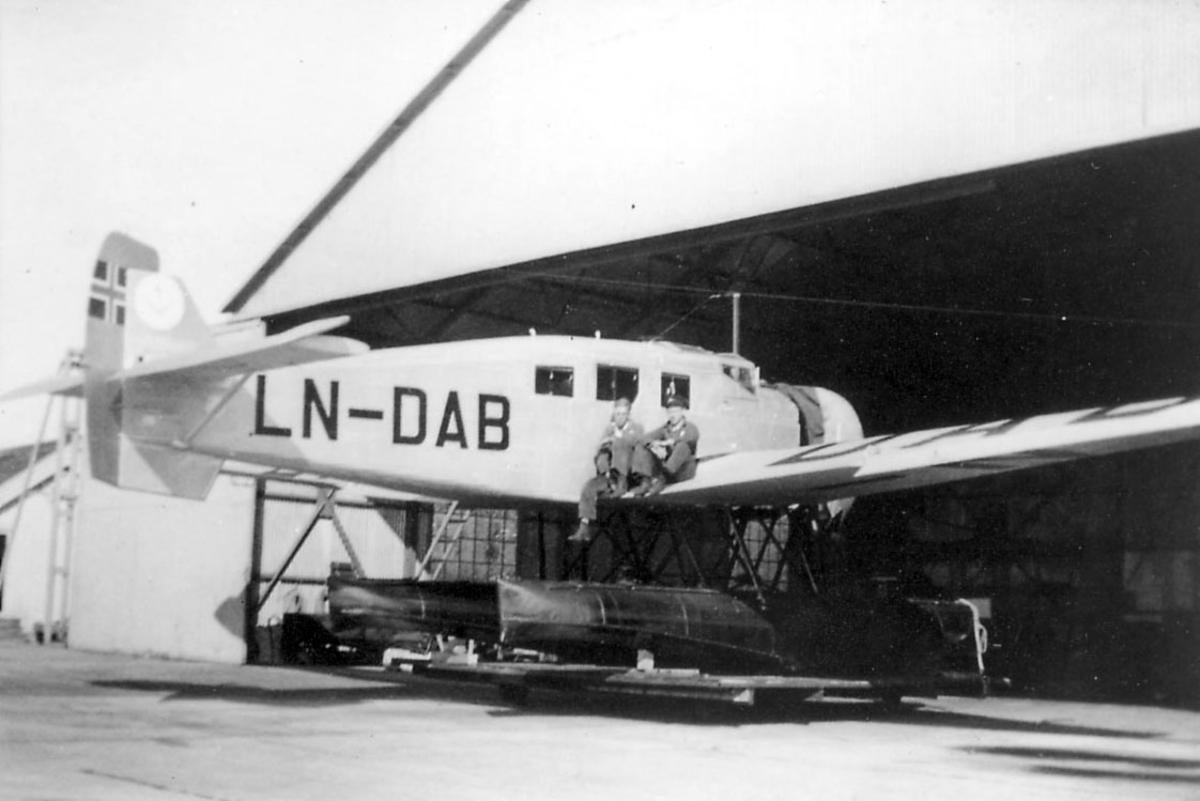 """Ant. sjøflyhavn. ett fly på bakken, Junkers Ju W 34 """"Ternen"""", LN-DAB, foran en hangarbygning. To personer sitter på den ene vingen."""