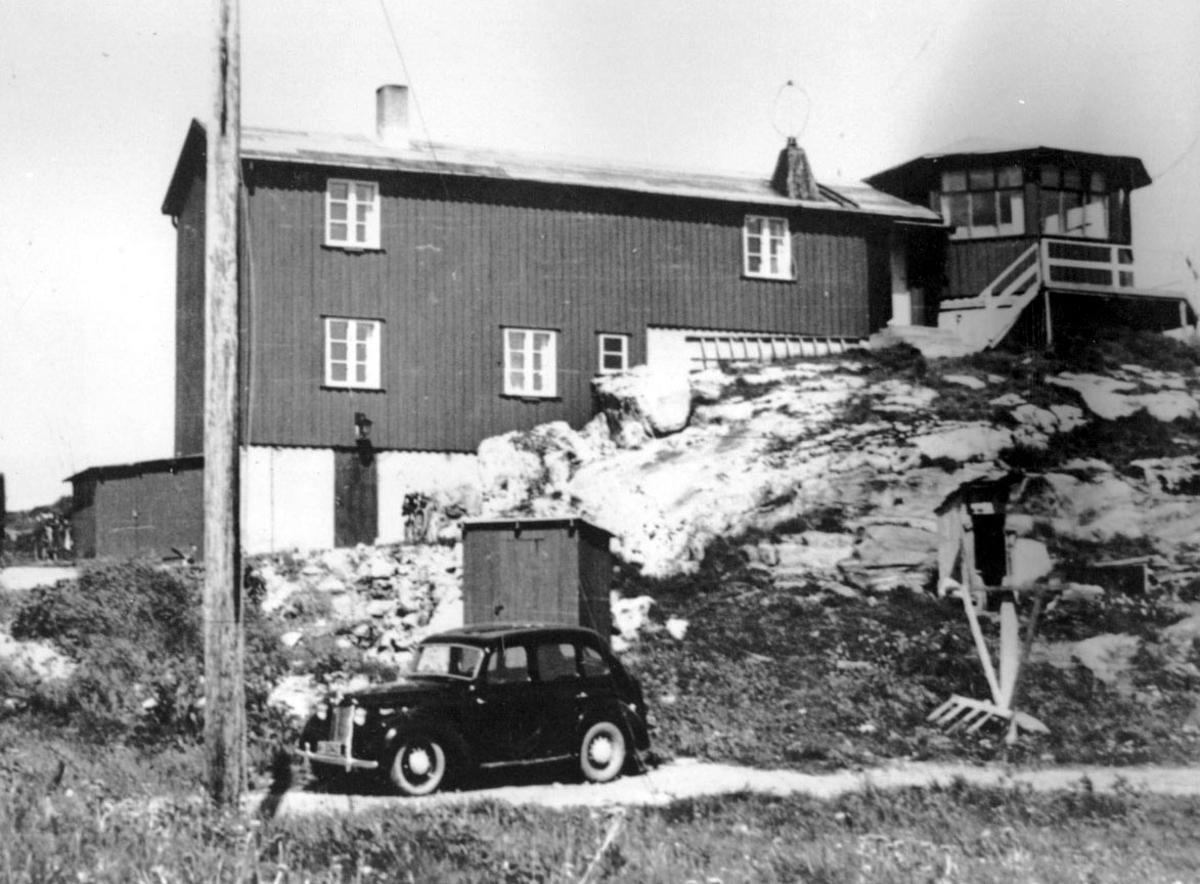 En bygning, kontrolltårn. ett kjøretøy, personbil nedenfor.