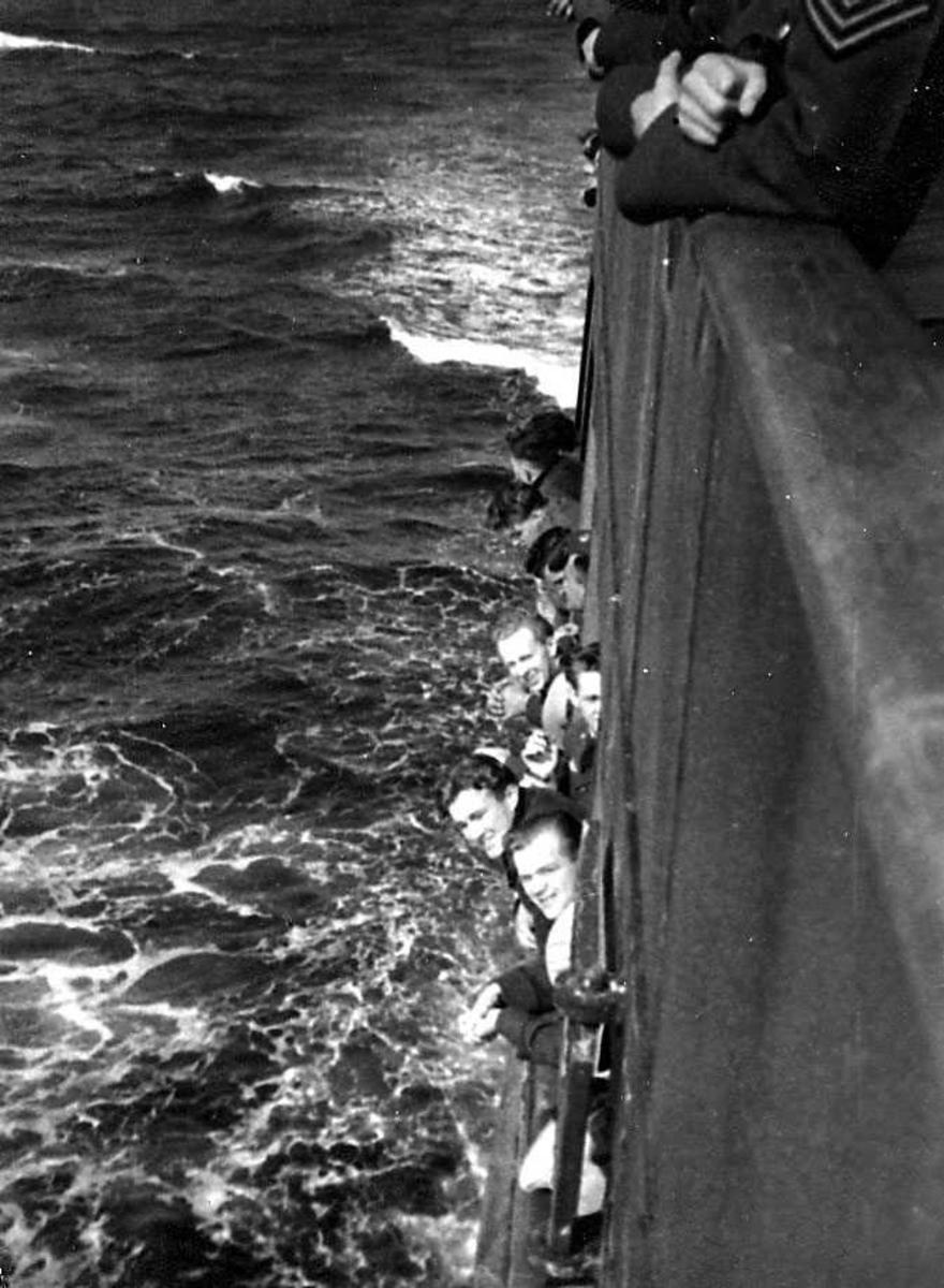 Flere personer, militære, i militæruniform. Ombord i en båt