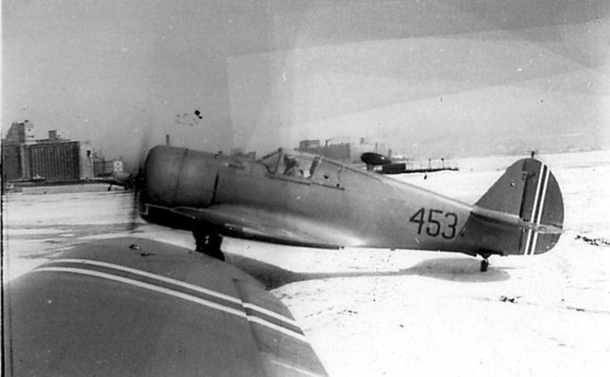 Åpen plass, ant. lufthavn. 1 fly, sett fra siden, merket 453. Vingen til et annet fly i forgrunnen. Snø på bakken Curtiss Hawk , Toronto