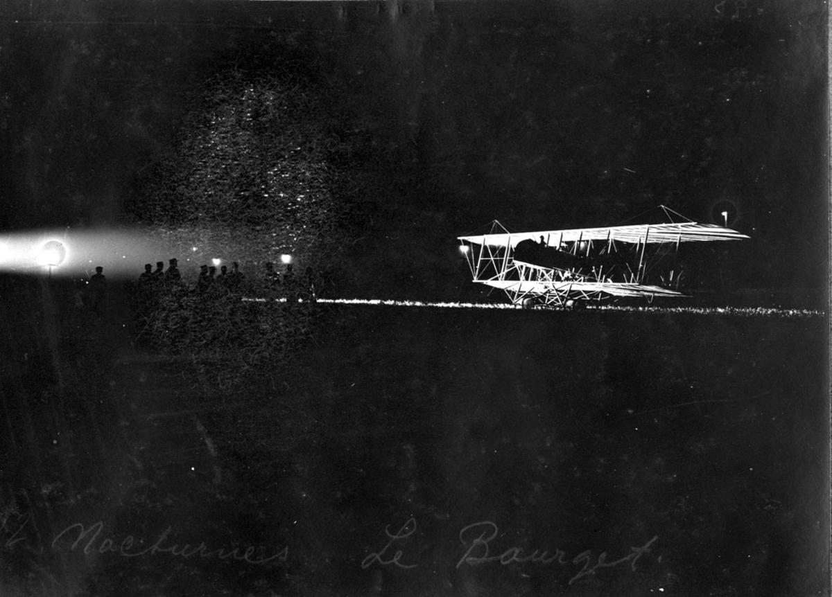 Fly, Maurice Farman. Står på bakken. Skrått forfra. Noen personer foran flyet. Bildet tatt i mørke, hvor flyet er flombelyst.