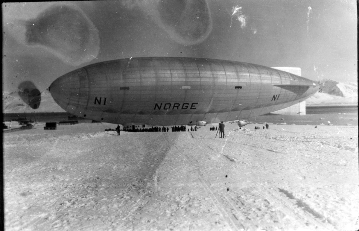 """Luftskipet """"Norge"""" rett før start på ferden over Nordpolen. Sett fra siden. Flere personer ved luftskipet. Snø på bakken. Noen bygninger, hav og fjell i."""