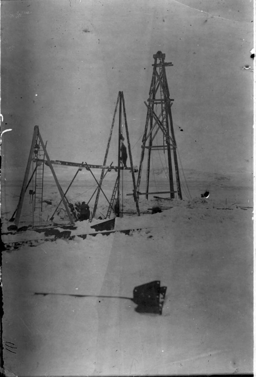 "Fortøyningsmasten til luftskipet ""Norge"". 2 tårn, heiseanordning, i forgrunnen. Snø på bakken."