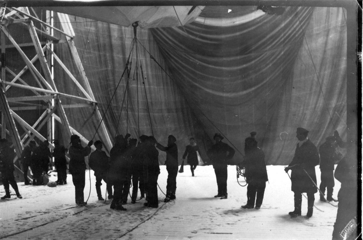 """Litt av luftskipet """"Norge"""" inne i hangaren, Flere personer i arbeid."""