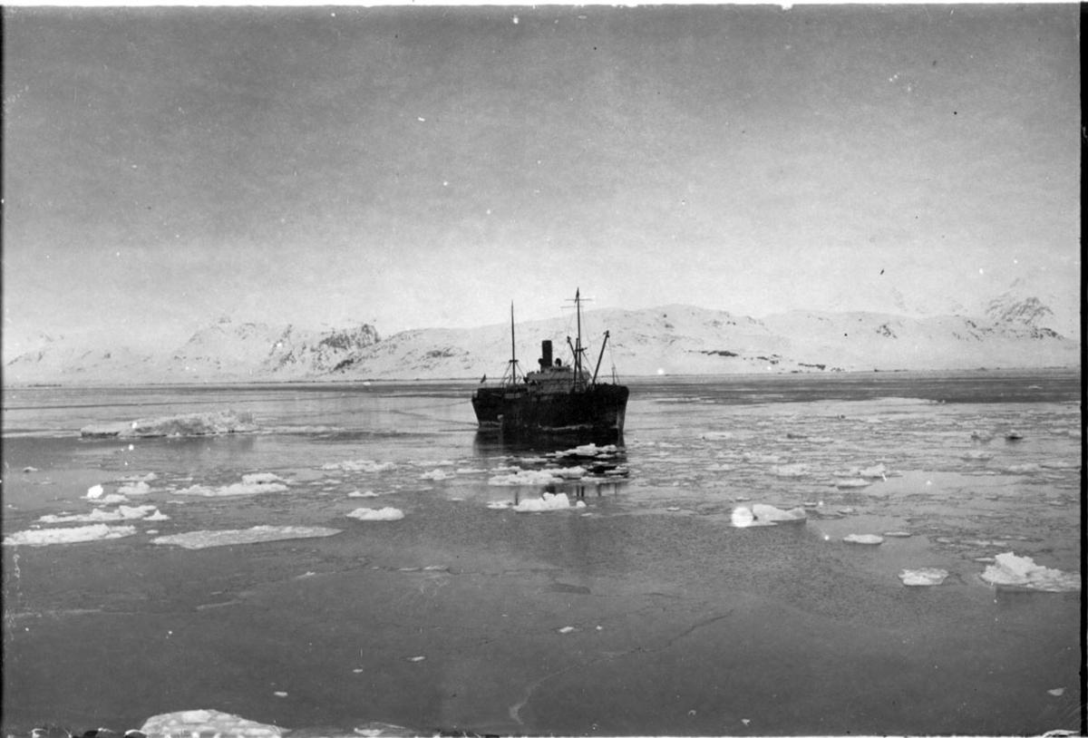 """Fartøy, båt, ute på fjorden, S/S """"Chantier"""". Små isflak på fjorden. Fjell bak."""