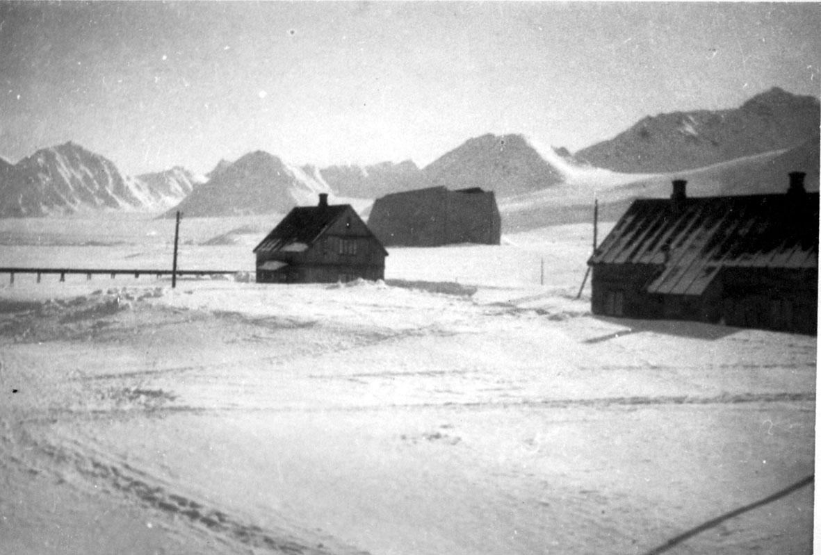 Luftskipshangaren bak, trukket med seilduk. 2 bygninger foran. Snø på bakken.