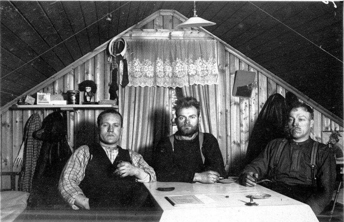 Portrett, 3 personer, tatt innendørs. Sitter ved et bord, vindu med gardiner, noen klær og hylle med div. utstyr på veggen bak.