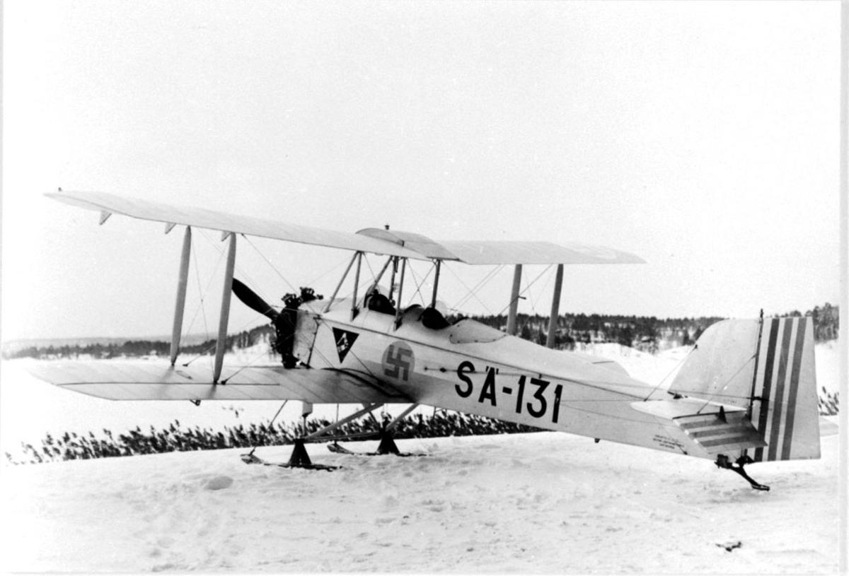 Fly, propellfly, dobbeldekker Sääski II, SA-131, med hakekors symbol på siden. Flyet med skiunderstell, står på bakken. Snø.