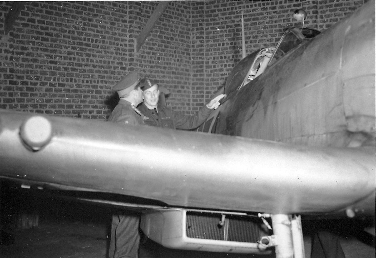 Fly inne i hangar e.l. 2 personer i militæruniform, studerer flyet.
