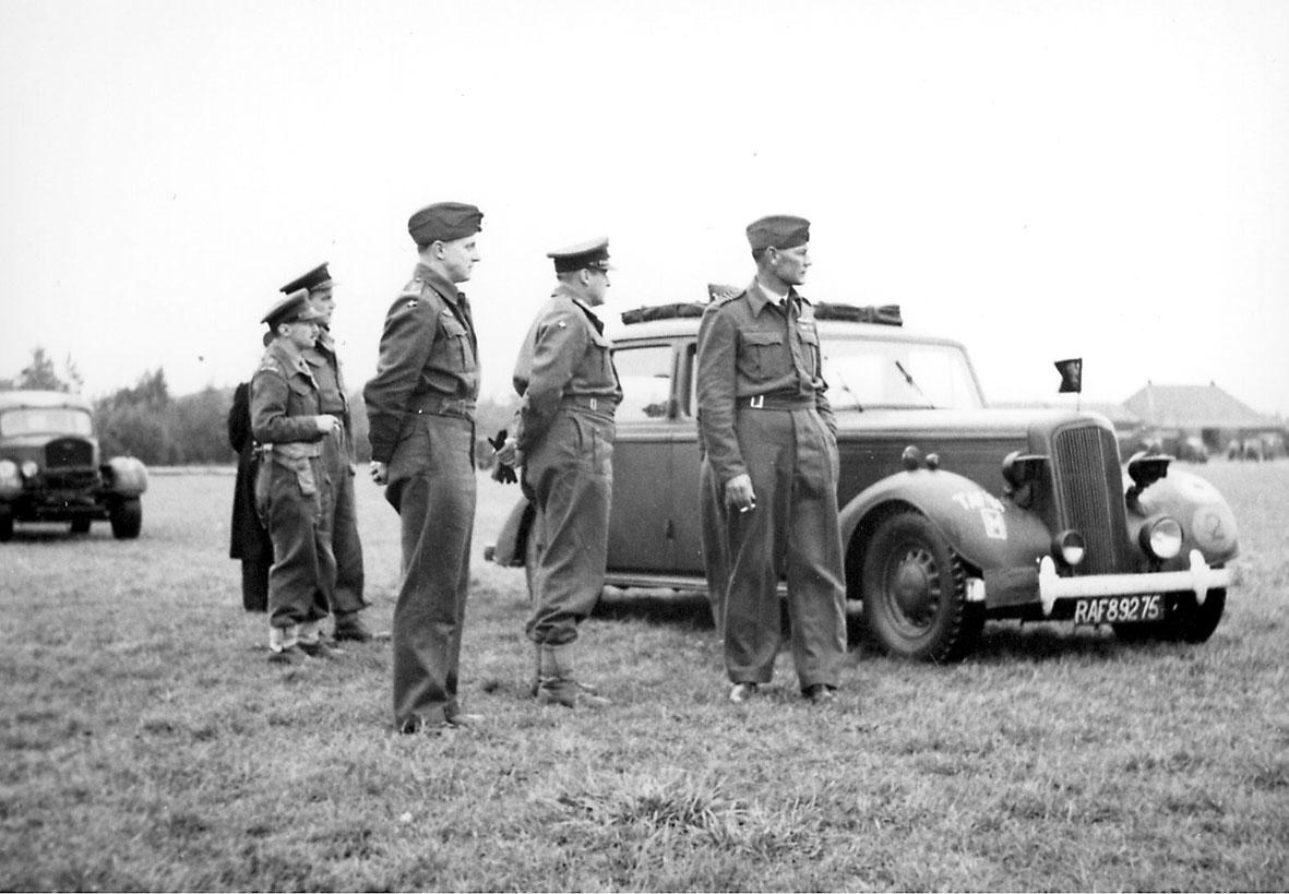 6 personer i militæruniform. Kronprins Olav sammen med 5 andre, på åpen plass. 2 biler, foran med nummerskilt RAF 89275