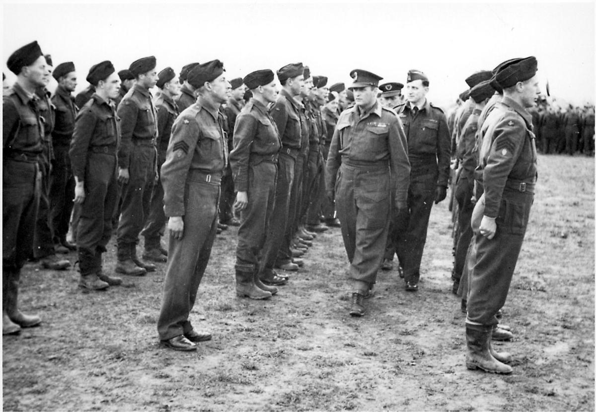 Militærtropp, soldater, står oppstilt på en åpen plass. Kronprins Olav inspiserer troppen.