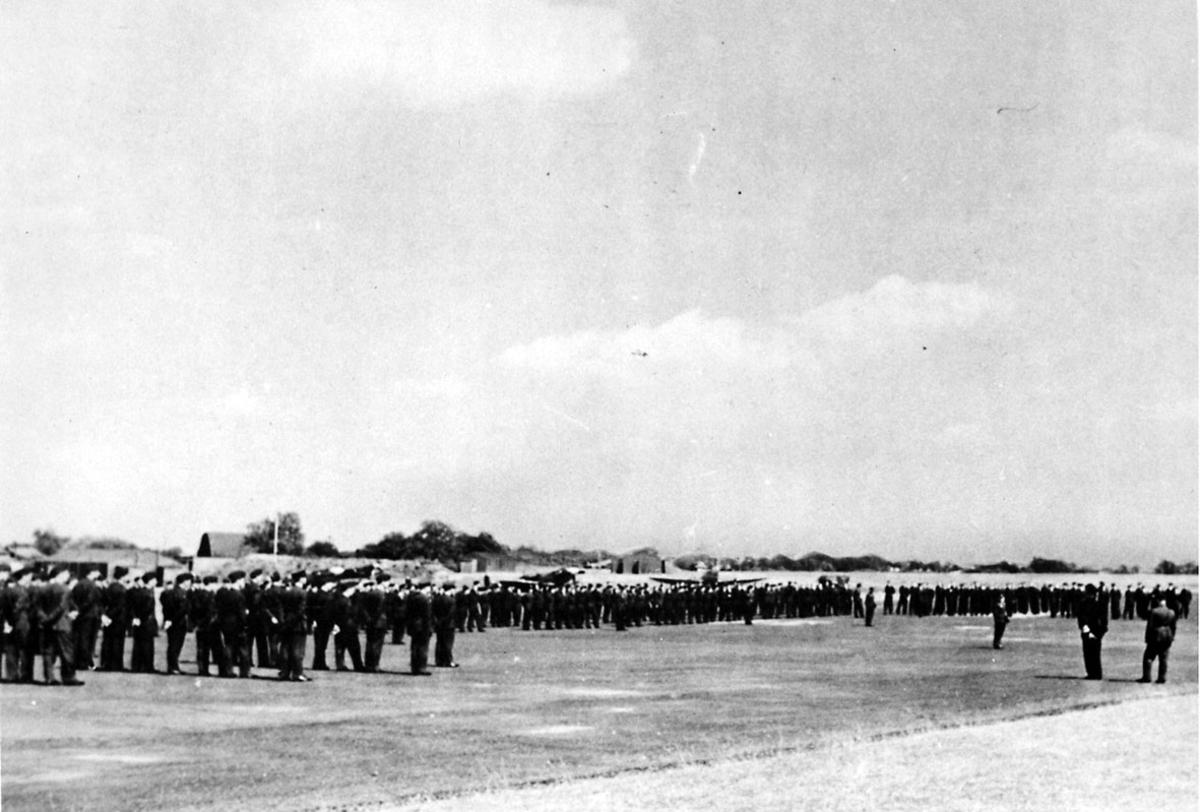 Større militærtropp oppstilt. Kong Haakon VII og Kronprins Olav sees foran. Inspeksjon av troppen. Noen fly, Spitfire og bygninger i bakgrunnen.