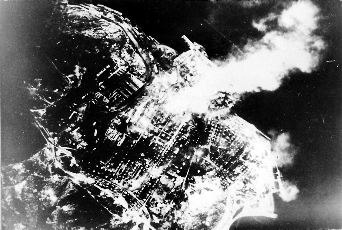 Luftfoto. Tettsted under, med røyk fra bygninger i brann etter bombing av området.