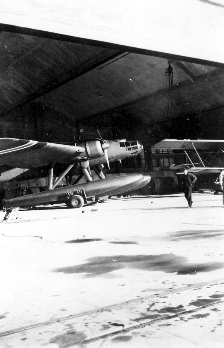 1 fly på bakken, ant. inne i hangar, Heinkel He 115 (N) A 2. Litt av annet fly t.h., dobbeldekker. 2 personer