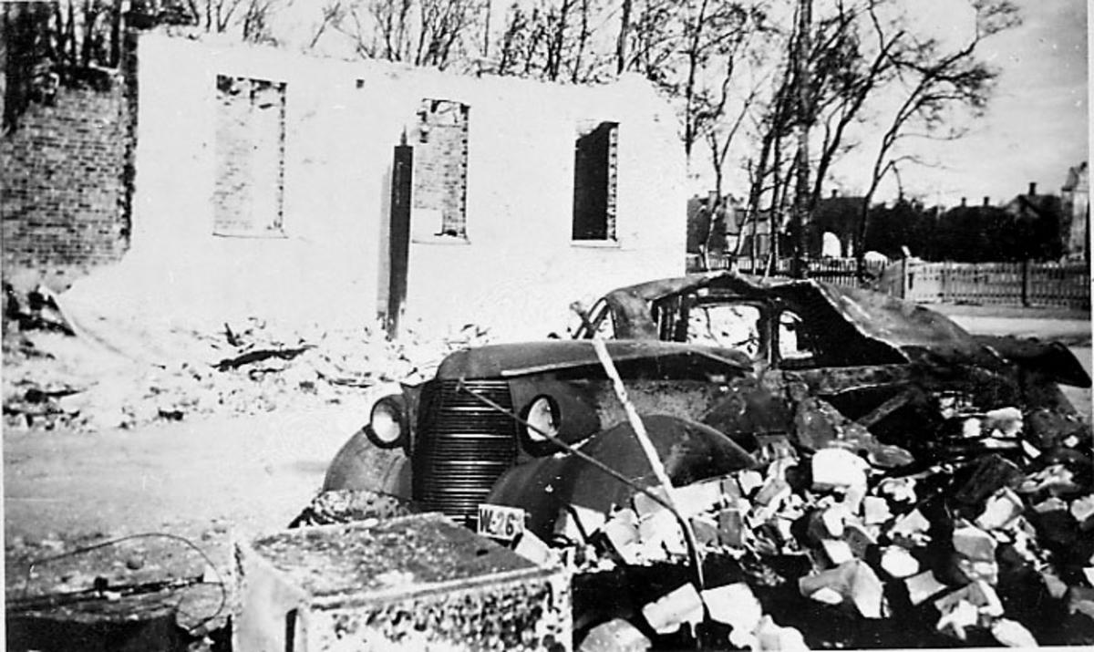 Ruin av bygning. Bodø etter bombingen under 2. verdenskrig. Bilvrak i forgrunnen, Studebaker 1938 med reg.nr. W-26