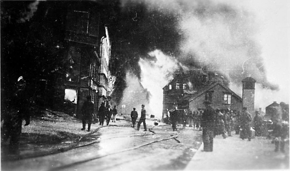 Røyk fra bygninger, i forgrunnen åpen plas med flere personer, slanger ligger utover. Narvik etter bombing - kriksødeleggelser, under 2. verdenskrig.
