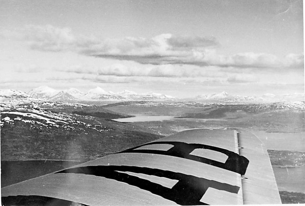 Luftfoto - kystlandskap - fjell og hav. Litt av flyvinge sees.