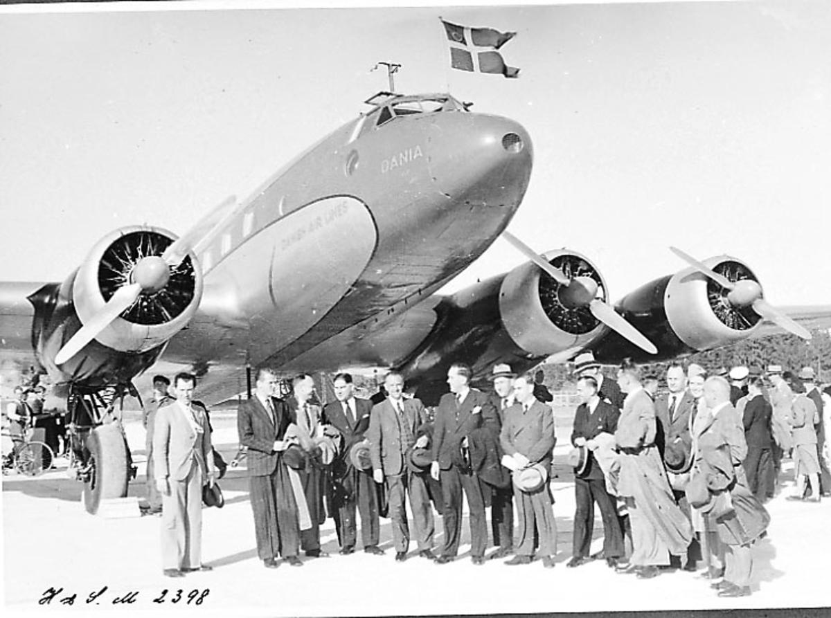 """Lufthavn, 1 fly på bakken, Focke-Wulf Fw200 Condor OY-DAM """"Dania"""" fra DAL (DDL). Flrere personer ved flyet."""