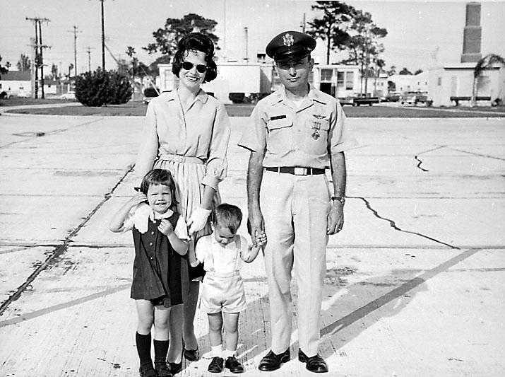 Familieportrett, 2 voksne og 2 barn. Mannspersonen ikledd militæruniform.