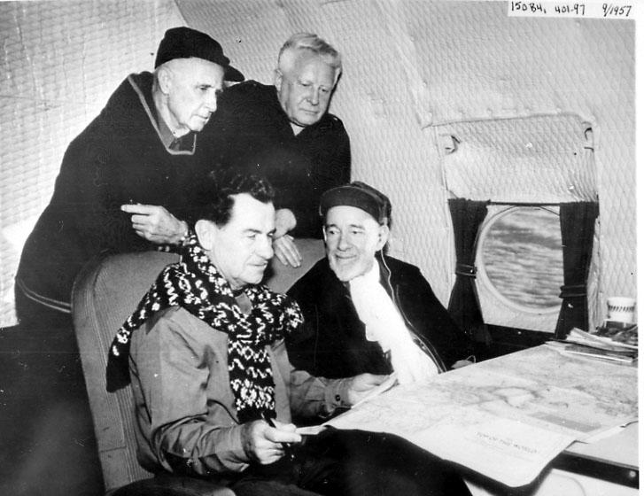 Portrett, 4 personer inne i et fly. Studerer et kart e.l. Flyet er ant. i lufta.