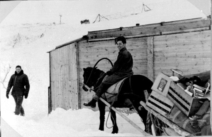 Portrett, 1 person i forgrunnen sitter på hesteryggen. Hesten trekker en slede lastet med utstyr. 1  person t.v.. Lita bygning bak. Tatt utendørs. Snø på bakken.