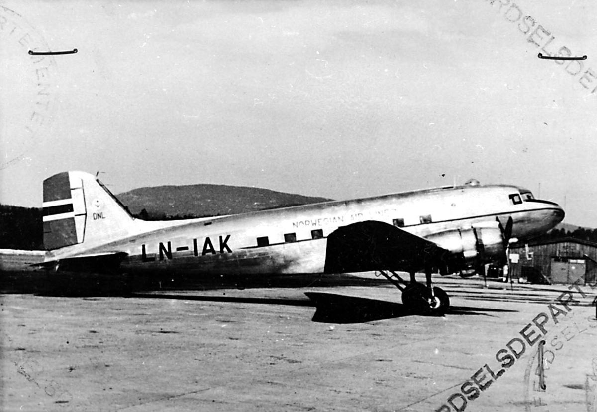 """Lufthavn, 1 fly på bakken, Douglas DC-3A C-53D, LN-AIK """"Knut Viking/ Nordkyn"""" fra DNL A/S Oslo. 1 hangarbygning i bakgrunnen."""