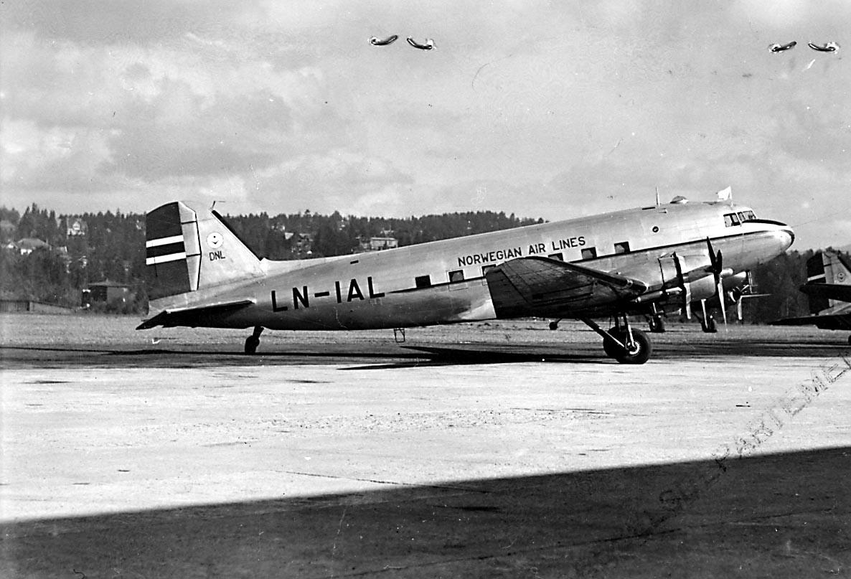 """Lufthavn, 1 fly på bakken, Douglas DC-3A C-53D, LN-AIL """"Erling Viking/ Nordlys"""" fra DNL A/S Oslo. Litt av flere andre fly i bakgrunnen."""