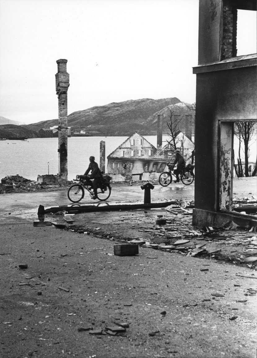 By - tettsted. Vei med to personer, menn i militæruniform på sykkel. Ruiner av flere bygninger. Hav - havneområde i bakgrunnen. Tyske soldater i Sjøgata.