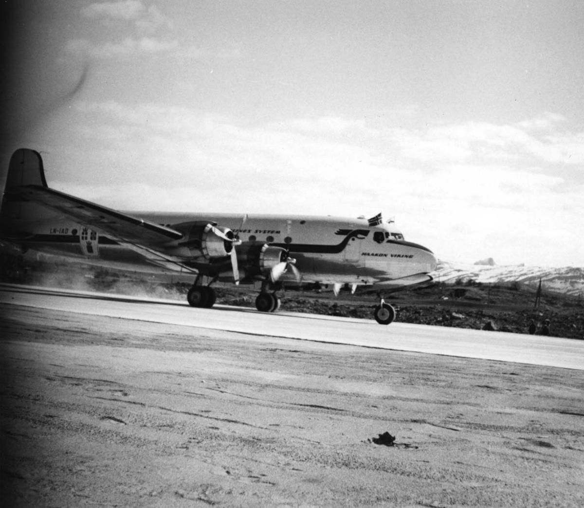"""Lufthavn, 1 fly på bakken, Douglas DC-4 /C-54-1009 Skymaster. Mil C-54 LN-IAD """"Haakon Viking fra DNL/SAS. Flere personer ved flyet."""