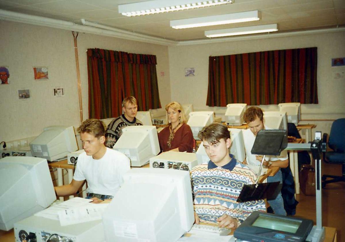 Gruppe. Fem personer ved dataskjermer i et klasserom.