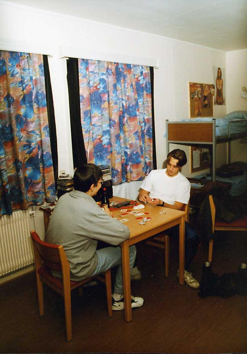Gruppe. To personer spiller kort på et forlegningsrom.