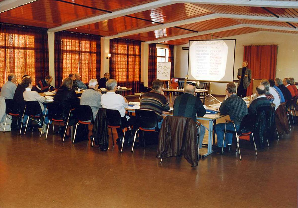 Gruppe. En person orienterer flere personer sitter ved et bord.