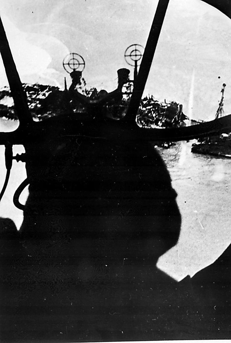 Luftfoto, 1 krigsskip med slagside, tatt fra cockpit på 1 jagerfly. Eksplosjon i vannet ved skipet.
