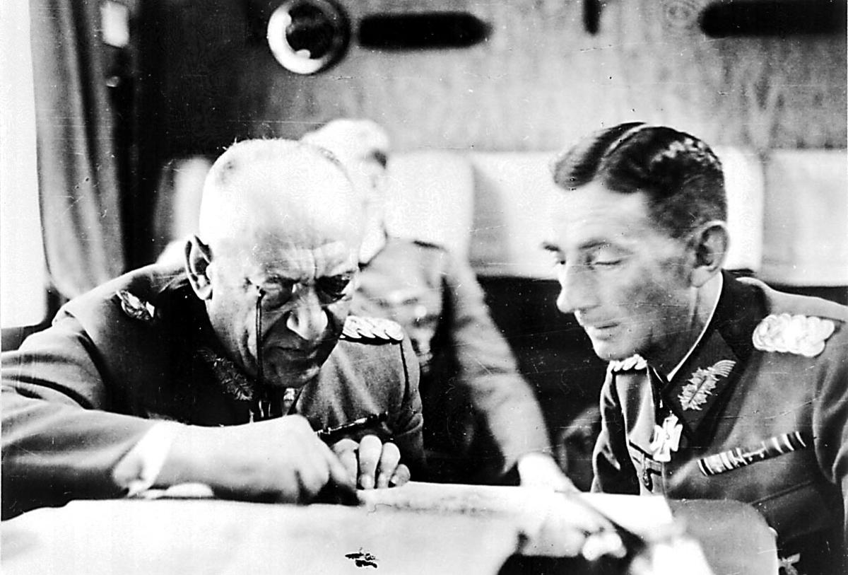 """Portrett, 2 personer, tyske militære, sitter og """"studerer"""" et notat/skriv/plan. 1 annen person, offiser, i bakgrunnen."""