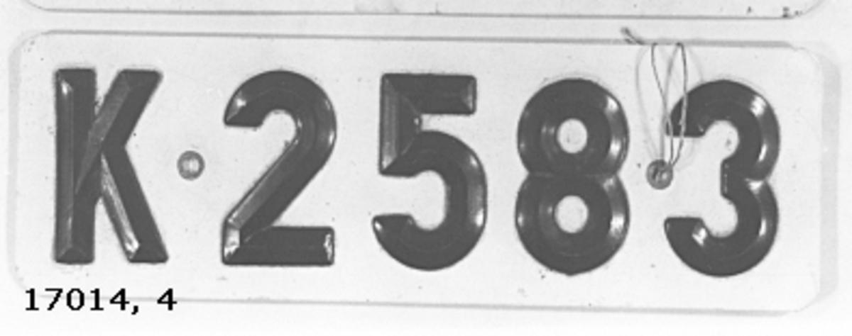 """Skylt av metallplåt ( aluminium ? ) målad vit på framsidan, svarta bokstäver och siffror av plast, fastnitade """" K 2583 """"."""