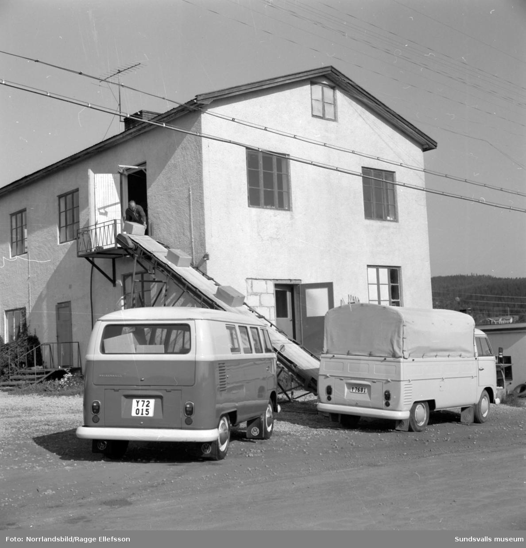 Stödebröd lastar sina VW-bussar för leverans. Brödkartongerna transporteras på ett finurligt transportband/rutchkana ner från övervåningen.