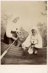 Två unga flickor poserar klädda i dräkt från Orsa, Dalarna m